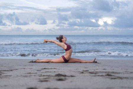 Photo pour Vue latérale de belle jeune femme pratiquant le yoga dans la pose des fentes avant (Hanumanasana) sur le bord de la mer - image libre de droit