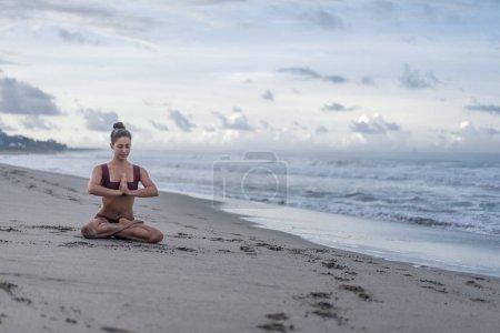 Photo pour Calme jeune femme pratiquant le yoga en pose de lotus (padmasana) sur le bord de la mer - image libre de droit