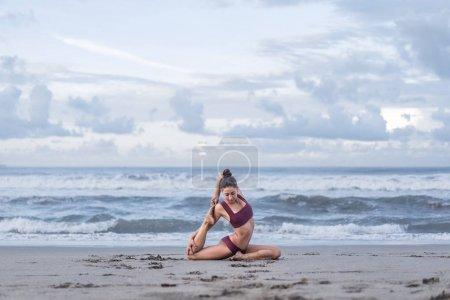 Photo pour Vue latérale du yoga pratique séduisante jeune femme dans un Pigeon pattes de King - sirène posent (Eka Pada Rajakapotasana) au bord de mer - image libre de droit
