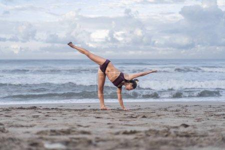 Photo pour Vue latérale du yoga pratique fit jeune femme en demi-lune posent (Ardha Chandrasana) au bord de mer - image libre de droit