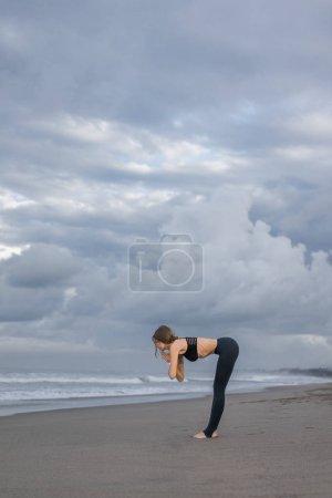 Photo pour Vue latérale du yoga pratique jeune femme dans l'ascenseur à mi-chemin posent (Ardha Uttanasana) au bord de mer - image libre de droit