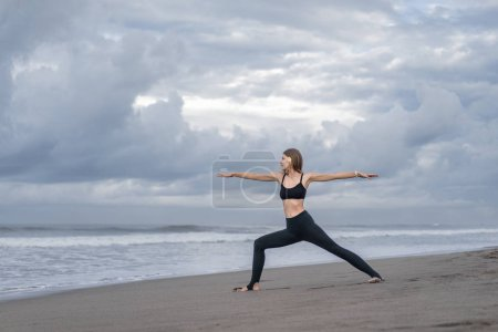 side view of beautiful young woman practicing yoga in Warrior pose (Virabhadrasana) on seashore