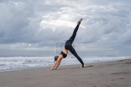 sporty young woman practicing yoga in One Legged Downward-Facing Dog pose (Eka Pada Adho Mukha Svanasana) on seashore