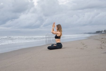 beautiful young woman practicing yoga in lotus pose on seashore on cloudy day