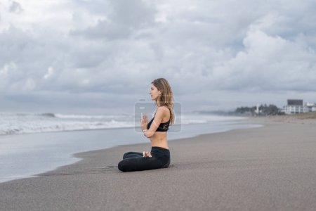 side view of beautiful young woman practicing yoga in lotus pose (padmasana) with namaste mudra on seashore