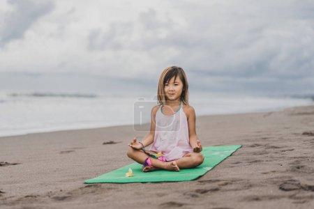 Photo pour Mignon petit yoga pratiquant d'enfant en lotus posent avec gyan mudra sur la plage de sable fin - image libre de droit