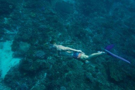 Photo pour Vue de côté du jeune homme en palmes de plongée sous-marine dans l'océan seul - image libre de droit