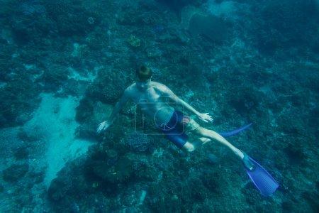 Photo pour Jeune homme en palmes plongeant seul dans l'océan - image libre de droit