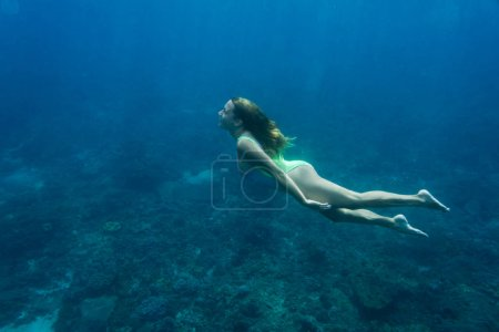 Photo for Underwater photo of young woman in swimming suit diving in ocean alone - Royalty Free Image