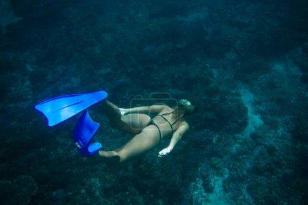Photo pour Vue arrière de la femme en bikini et palmes plongeant dans l'océan seul - image libre de droit