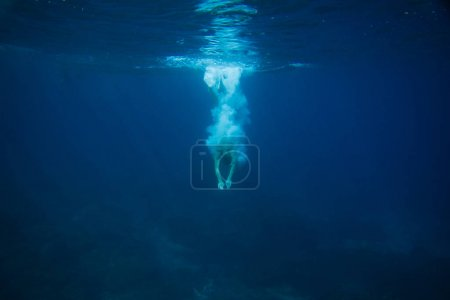 partial view of man diving into ocean