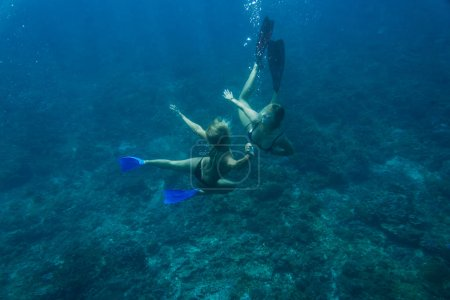 Photo for Underwater photo of young friends in bikinis diving in ocean - Royalty Free Image