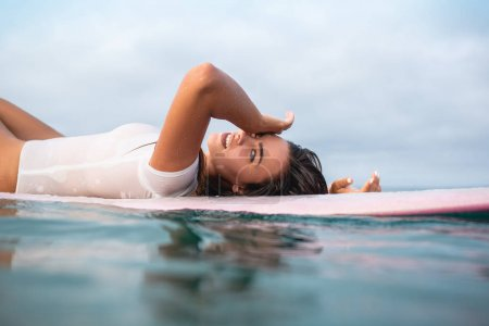 beautiful young woman relaxing on surfboard in ocean during summer vacation
