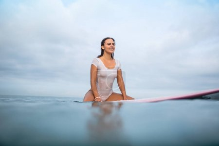 smiling attractive woman in white wet swimsuit sitting on surfboard in ocean during summer vacation