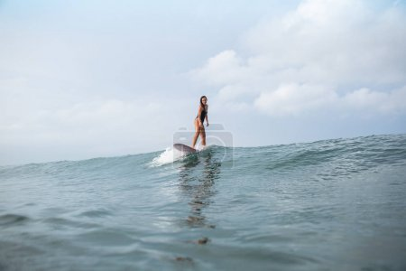 attractive young woman standing on surfboard in ocean
