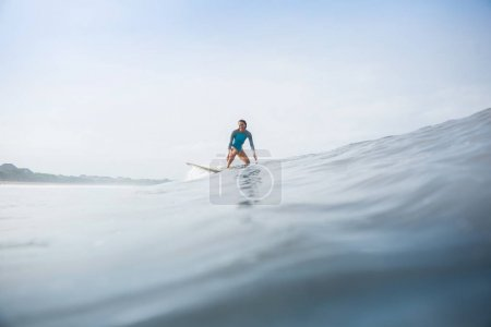 young woman in sportive swimsuit riding surfboard in ocean