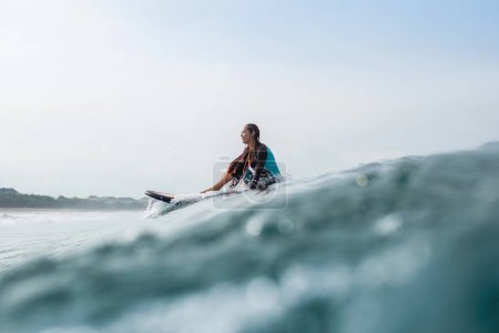 beautiful young woman sitting on surfboard in ocean