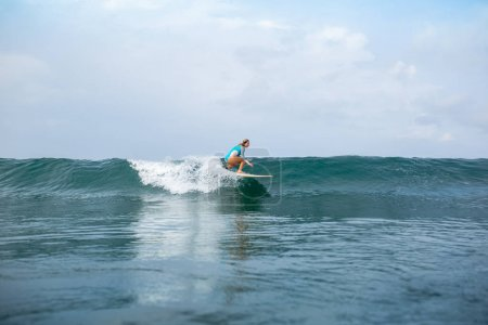athletic young woman in sportive swimsuit riding surfboard in ocean during summer vacation