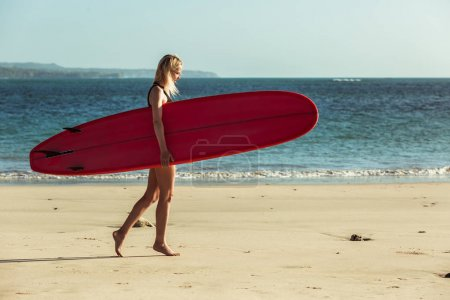 female surfer holding surfboard and walking on beach near the sea