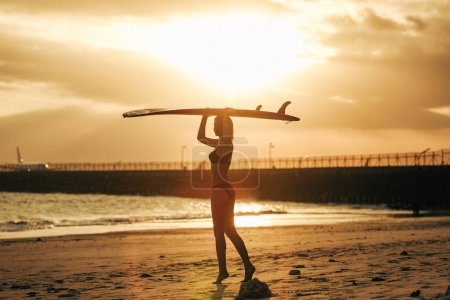 woman posing with surfboard on head on resort at sunset