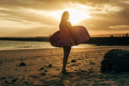 female surfer posing with surfboard on beach at sunset with back light