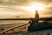woman sitting on rock with surfboard on beach at sunset with airplane in sky