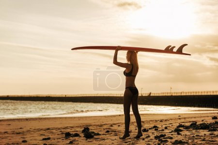 female surfer posing with surfboard on head at sunset