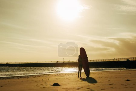 back view of surfer posing with surfboard on beach at sunset