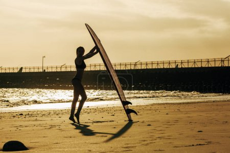 silhouette of female surfer posing with surfboard on beach at sunset