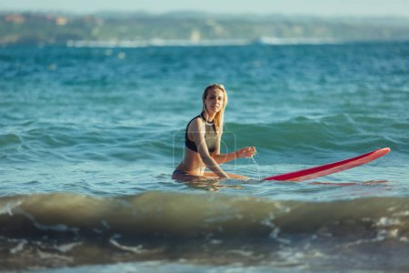 attractive female surfer sitting on surfboard in ocean
