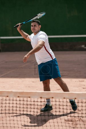 Handsome young man on tennis court. Man playing te...