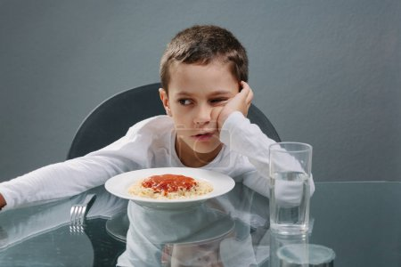 Photo for Portrait of child with no appetite in front of the meal. Concept of loss of appetite - Royalty Free Image