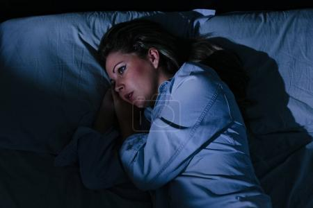 Photo for Sleep disorder, insomnia. Young blonde woman lying on the bed awake - Royalty Free Image