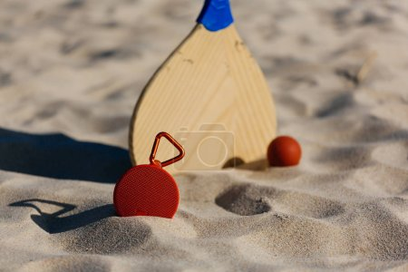 Photo for Wireless portable speaker and beach tennis rackets on the beach - Royalty Free Image
