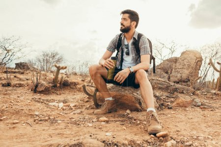 Young man relaxing and enjoying the ambience after long hike in the desert