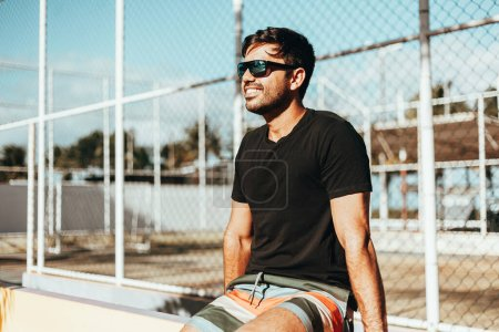 Photo for Portrait of smiling man wearing sunglasses and t-shirt enjoying a sunny summer day in the city - Royalty Free Image
