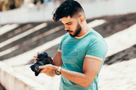 Photo for Young man with DSLR camera in city - Royalty Free Image