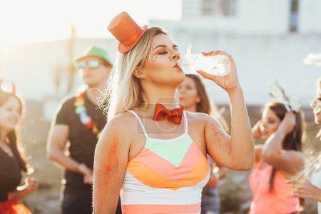 Photo pour Carnaval brésilien. Une femme en costume d'époque boit de l'eau - image libre de droit