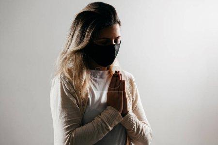 Photo pour Femme portant un masque facial pour protéger le coronavirus covid-19. Prier à la maison, Église en ligne, Prier les mains, Culte à la maison . - image libre de droit