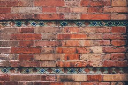 mur de briques vieilli décoré avec des tuiles bleues pour le fond