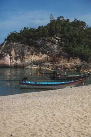 Photo pour Côte rocheuse près de plage de sable avec vieux bateau journée ensoleillée - image libre de droit