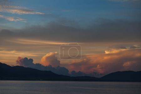 Photo for Beautiful sunset cloudy sky over sea and hills - Royalty Free Image