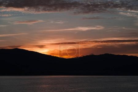 beautiful sunset over silhouette of hills and water surface