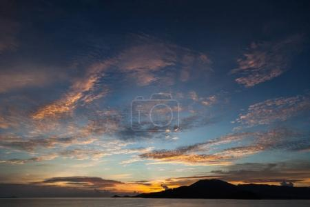 tranquil sunset seascape under cloudy sky
