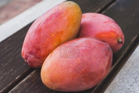 sweet ripe mango fruits over wooden table