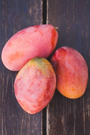 Photo for Sweet ripe mango fruits over wooden table - Royalty Free Image