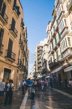 view of spanish street with people under blue sky