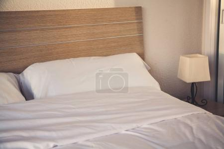 hotel room interior with bed and lamp