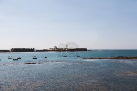 Scenic view of seascape with pier and boats under blue clear sky, Cadiz.