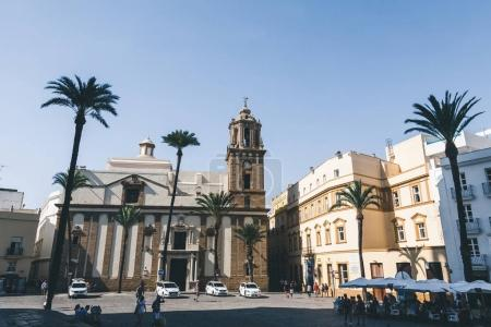 view of street with church, palms and automobiles, spain